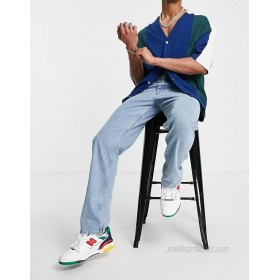 DESIGN straight leg jeans in mid wash blue with bum rip